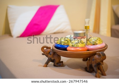 Spa massage setting with thai herbal compress stamps and candlelight in massage room - stock photo