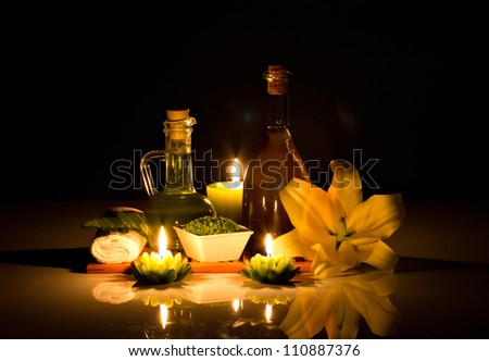 Spa oil, candles, flowers and spa cosmetics on black background - stock photo