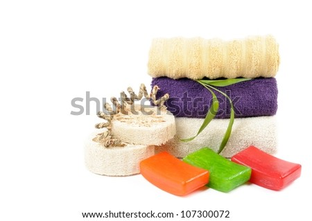 Spa or bathroom concept with towels and soaps, on a white background