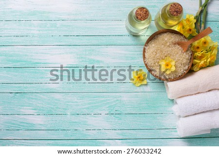 Spa or wellness setting. Sea salt in bow, aroma oil, towels and yellow flowers on turquoise painted wooden background. Selective focus. Place for text. - stock photo