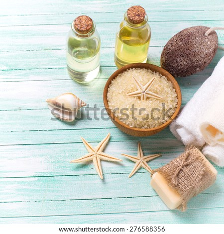 Spa or wellness setting. Sea salt in bowl, soap, aroma oil, pumice, towels and sea objects  on turquoise painted wooden planks. Selective focus is on sea salt. Square image. - stock photo