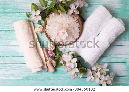 Spa or wellness setting. Sea salt in bowl, towels and apple blossom on turquoise  painted wooden background. Selective focus is on salt.
