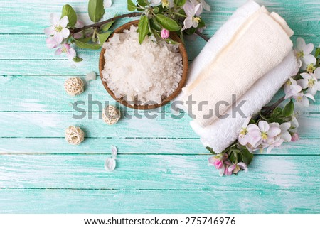 Spa or wellness setting. Sea salt in bowl, towels and apple blossom on turquoise wooden background. Selective focus is on salt. - stock photo