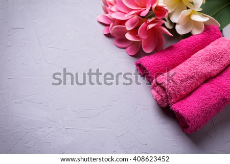 Spa or wellness setting. Set of  pink bath towels  and tropical flowers on grey textured background. Selective focus. Place for text. - stock photo