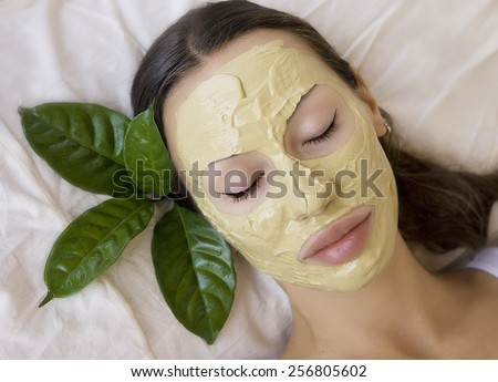 Spa Outdoor, Beautiful young woman lying with natural Indian Multani Matti clay facial mask on her face, skin care and wellness - stock photo