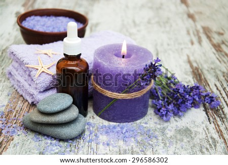 Spa products and lavender flowers on a wooden background
