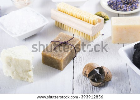 spa products: black mud and clay powder, cosmetic cream, soap, bath salt, shea butter and lavenders on white wood table background