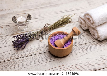 Spa products on the wooden table: lavender, candle, sea salt, sea salt bowl, towels. - stock photo