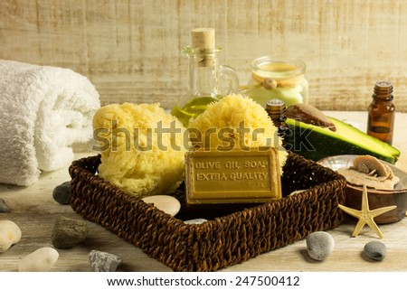 spa products stones with massage oil - green leaf background - stock photo