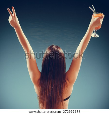 Spa relax and holidays concept. Happy woman in swimsuit back view. Fit female body, girl long hair at poolside with cocktail glass arms raised up in celebration - stock photo