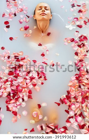 Spa Relax In Flower Bath. Woman Health And Beauty. Closeup Beautiful Sexy Girl Bathing With Rose Petals In Renew Day Spa Salon. Beauty Treatment, Aromatherapy Skin Body Care Therapy. Wellness Concept - stock photo