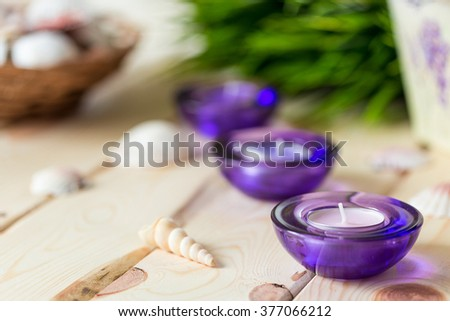Spa Relax Set, Aromatic Candles in Purple Glass Candlesticks, Green Grass and Shells on Light Wooden Background - stock photo