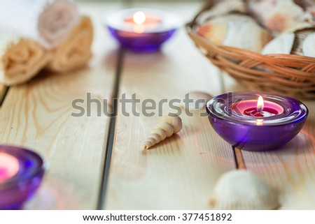 Spa Relax Set, Towels, Aromatic Candles in Purple Glass Candlesticks Shells on Light Wooden Background - stock photo