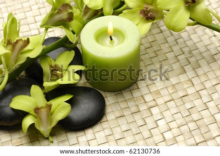 Spa resort composition - candles, orchid flowers and zen stones on straw mat - stock photo
