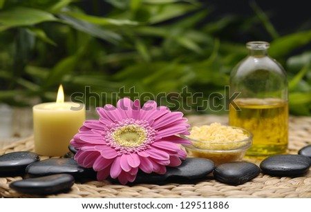 spa salt in spoon with orchid and flower with candle, green leaf on wicker mat