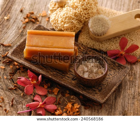 Spa set in bowl with dry flower petals on old wood - stock photo