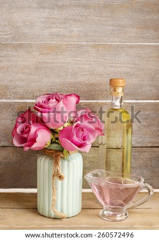 Spa set: liquid soap and bottle of essential oil. Bouquet of pink roses and blue muscari flower (Grape Hyacinth)., copy space - stock photo