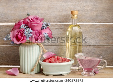 Spa set: sea salt, liquid soap and bottle of essential oil. Bouquet of pink roses and blue muscari flower (Grape Hyacinth). - stock photo
