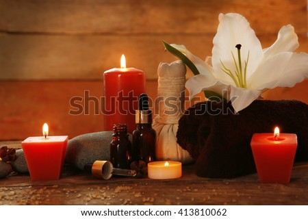 Spa set with lighted candles on wooden background