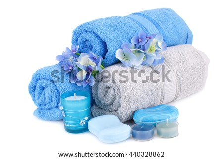 Spa set with towels, candles, flowers and various soaps isolated on white background. - stock photo