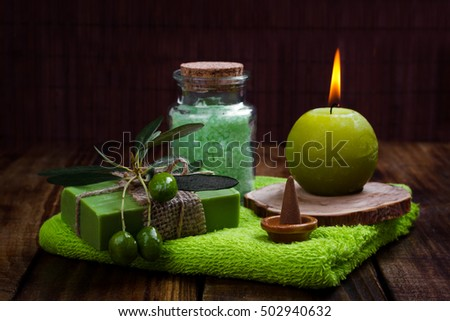Spa setting and health care items, handmade olive oil soap,bath salt,candle, towels on wooden board