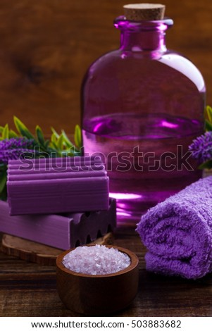 Spa setting and health care items, lavender handmade soap,body oil,bath salt, towel, on wooden board