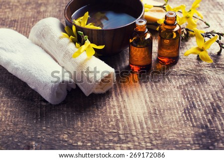 Spa setting. Essential aroma oil , water in bowl, towels, yellow flowers on aged wooden background. Selective focus. Place for text. Toned image. - stock photo