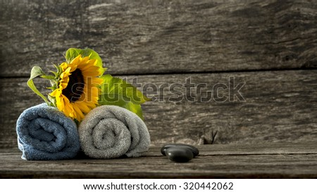 Spa setting for a couple - two rolled towels with beautiful blooming sunflower on top and two black spa stones lying on textured rustic wooden ambient. - stock photo