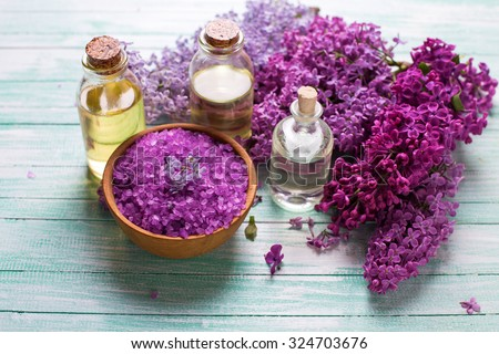 Spa setting. Organic aroma oils, sea salt,  lilac flowers  on turquoise painted wooden planks. Selective focus.  - stock photo