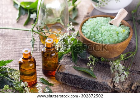 Spa setting. Sea salt and organic essential aroma oil with mint  on aged wooden background. Selective focus.  - stock photo