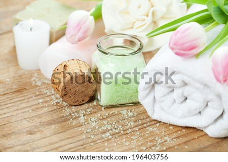 Spa setting with bath accessories and pink tulips on wooden background