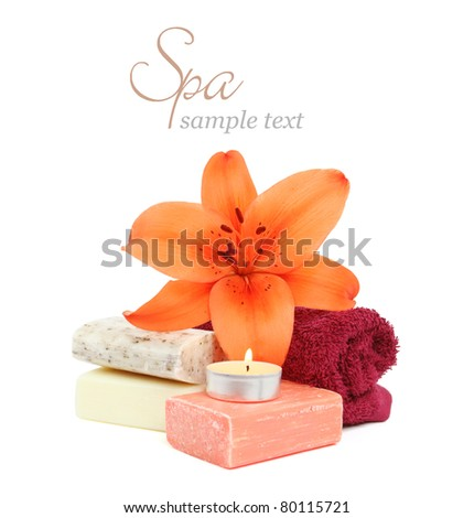 Spa setting with candle, flower, towel, and natural soap over white background