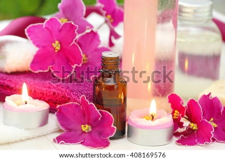 SPA setting with candles, aroma oil and fresh violets - stock photo