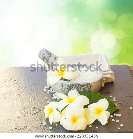 Spa setting with fresh frangipani  flowers and towels  in green garden