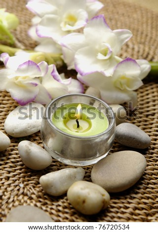 Spa setting with Gardenia, candles, and pebbles - stock photo