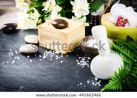 Spa setting with herbal massage ball, flowers and essential oil. Wellness concept - stock photo
