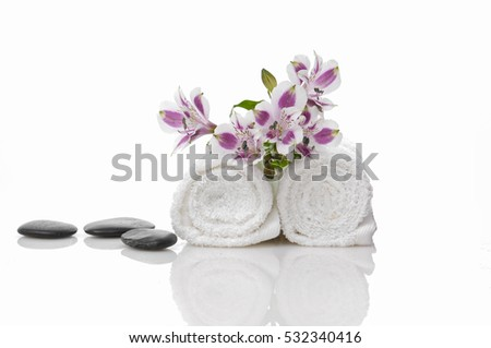 Spa setting with orchid , roller towel, black stones
