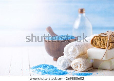 Spa setting with soap, towels, sea salt and aroma oil in ray of light on white  painted wooden boards. Selective focus. - stock photo