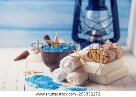 Spa setting with soap, towels, sea salt on  painted wooden boards. Selective focus.Toned image. - stock photo