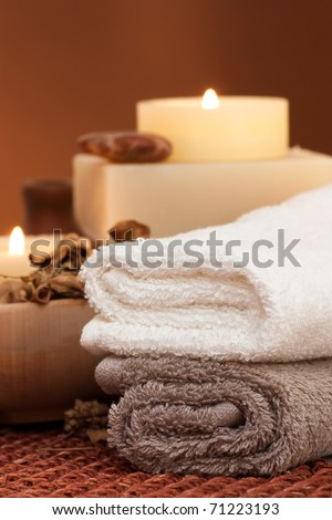 Spa setting with towels and candle - stock photo