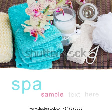 spa setting with  towels, aroma candle and bath accessories on white - stock photo