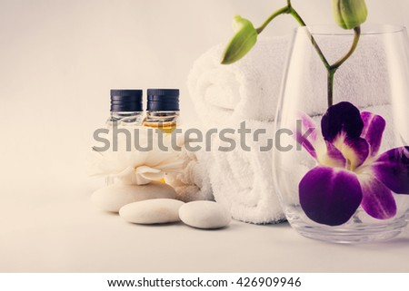 Spa setting with towels aroma oil bottles orchid and hand made flower, warm light in sauna. - stock photo