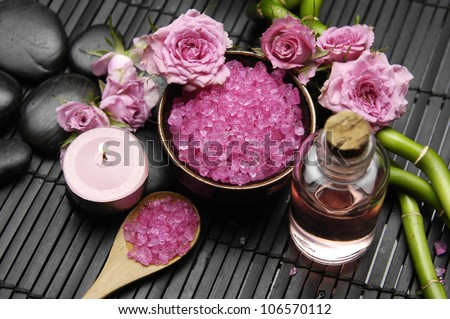 spa settings �pink rose with salt in bowl and candle with bamboo grove on mat - stock photo