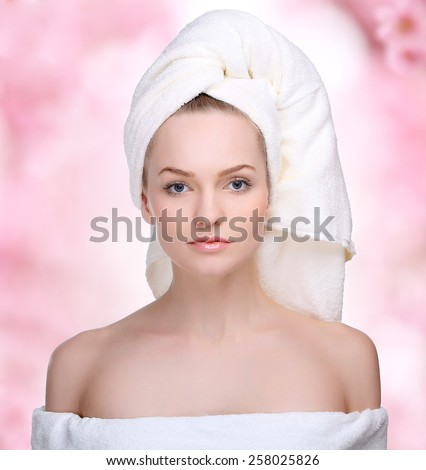 Spa skin care beauty woman wearing hair towel after beauty treatment. Beautiful multiracial young woman with perfect skin on pink background.  - stock photo