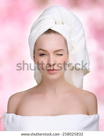 Spa skin care beauty woman wearing hair towel after beauty treatment. Beautiful multiracial young woman with perfect skin isolated on pink background. - stock photo