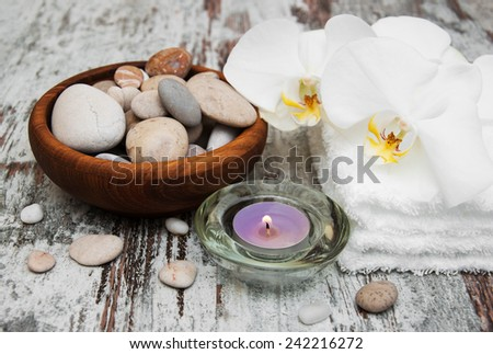 spa still life - a flower and towels on a wooden background