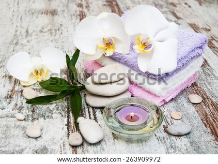 spa still life - a flowers  and towels  Ion a wooden background - stock photo