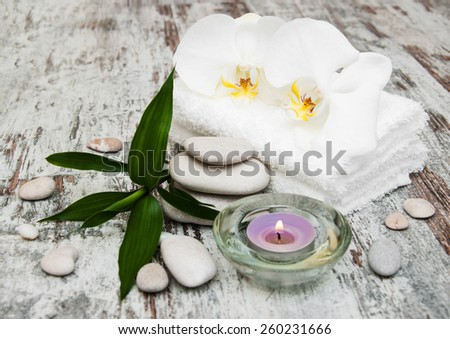 spa still life - a flowers  and towels  on a wooden background