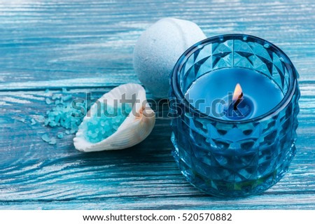 SPA still life, closeup of blue lit candle, salt and bath bombs on wooden background. Space for text