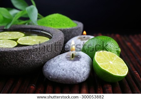 Spa still life in green color on bamboo mat on dark background - stock photo